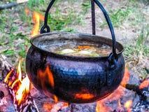 Suppe, die in einem kupfernen Kessel auf dem Feuer kocht Lizenzfreie Stockfotografie