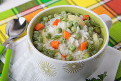 Suppe mit Reis, Karotten und grünen Erbsen Stockbild