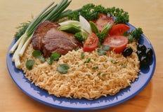 Suppennudeln, Nudeln mit Rindfleischsteak auf einer blauen Platte, verziert mit geschnittenen Tomaten, schwarze Oliven lizenzfreie stockbilder