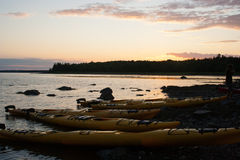 Supper Break. A group of kayak paddlers stop for a meal along the shore in Acadia National Park, Maine. Sunset stock photos
