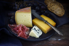 Supper plate with various cheese, air dried ham, blue grapes and Royalty Free Stock Photo
