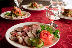 Supper in restaurant. Ham and sausage on plate in restaurant Royalty Free Stock Photos