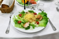 Supper at restaurant. Green salad with meat. Table setting royalty free stock image