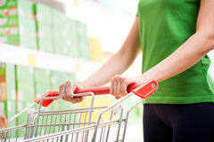 Supping cart and supermarket shelf. Young woman with shopping cart at supermarket hands close-up Royalty Free Stock Photography