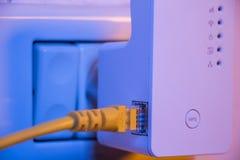Supplément de WiFi dans la prise électrique sur le mur avec la cabine d'Ethernet Photos libres de droits