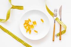 Supplément diététique pour le bien-être L'huile de poisson ou les capsules omega-3 sur bande de mesure proche de plat sur le fond Photographie stock
