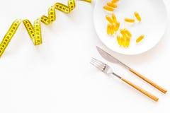 Supplément diététique pour le bien-être L'huile de poisson ou les capsules omega-3 sur bande de mesure proche de plat sur le fond Photo stock
