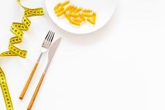 Supplément diététique pour le bien-être L'huile de poisson ou les capsules omega-3 sur bande de mesure proche de plat sur le fond Image stock