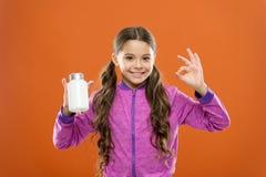 Suppléments de vitamine de prise Formule de multivitamin complet et d'enfants minéraux Bouteille de médecines de prise de fille v photographie stock libre de droits