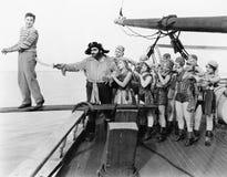 设法小组的海盗推挤在板条的一个年轻人(所有人被描述不更长生存,并且庄园不存在 suppl 免版税图库摄影