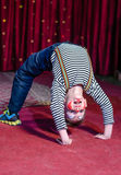 Supple agile little boy doing a back arch. Supple agile little boy doing back arch handstand stage theatre wearing his colorful makeup grins  camera from upside Royalty Free Stock Image