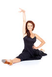 Supple fashionable woman doing the splits. Beautiful supple fashionable woman doing the splits in a black cocktail dress and high heels and smiling at the camera Royalty Free Stock Photo