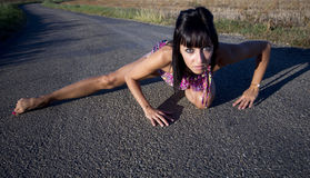 Supple woman crouches on a country road. Stock Photography
