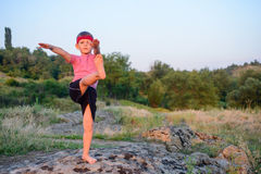 Supple young boy practicing pilates outdoors. Standing barefoot balancing on one leg on a rock in the countryside with a look of concentration in a health and Royalty Free Stock Images