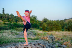 Supple young boy practicing pilates outdoors. Standing barefoot balancing on one leg on a rock in the countryside with a look of concentration in a health and Royalty Free Stock Photo