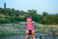 Supple young boy practicing pilates outdoors. Standing barefoot balancing on one leg on a rock in the countryside with a look of concentration in a health and Stock Image
