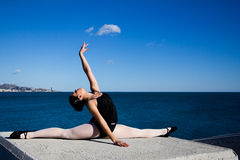 Supple young dancer does the splits on a big stone block. Royalty Free Stock Image