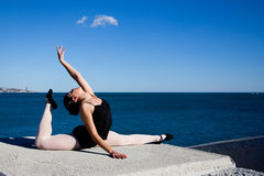 Supple young dancer does the splits on a big stone block. In Malaga, a supple young dancer does the splits on a big stone block. She raises one arm to a cloud Royalty Free Stock Photo