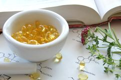 Supplement. Cupsules with herbs and book Stock Photos