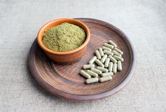 Supplement kratom green capsules and powder on brown plate. Herb. Al product alt-medicine kratom is  opioid. Home alternative pain remedy, opioid addiction Royalty Free Stock Images