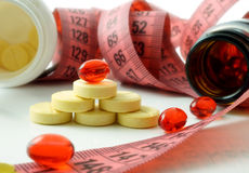 Supplements of diet. Measuring tape and bottle with pills. supplements of diet Royalty Free Stock Image
