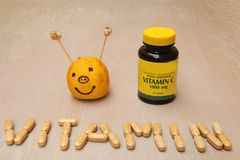 Supplements jar and a vitamin sign created from vitamin pills Stock Images