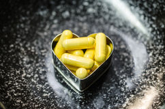 Supplemnet amarillo CoQ10 de la comida en la placa negra Fotos de archivo