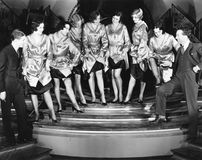 炫耀他们的腿的妇女一排合唱对两个人(所有人被描述不更长生存,并且庄园不存在 Suppli 库存照片