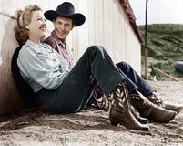 在西部服装的笑的夫妇坐地面(所有人被描述不更长生存,并且庄园不存在 Suppli 免版税库存照片