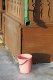 The supplied plastic bucket collects melt water from the downpour. Of the village house Stock Photo