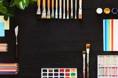 Creative art painting drawing supplies tools set on wooden desk top view. Supplies set on desk top view, creative tools for school creative work on black wooden royalty free stock photos