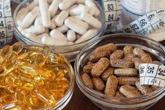 Suppléments nutritionnels dans les capsules et des comprimés, sur le fond en bois Images libres de droits