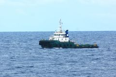 Supply boat support oil and gas industry. Supply boat transfer cargo to oil and gas industry and moving cargo from the boat to the platform. Boat is waiting royalty free stock photo