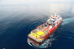 Supply boat transfer cargo to oil and gas industry and moving cargo from the boat to the platform, boat waiting transfer cargo Stock Image
