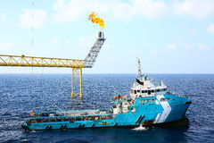 Supply boat transfer cargo to oil and gas industry and moving cargo from the boat to the platform, boat waiting transfer cargo. And passenger between oil and stock images