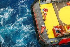 Supply boat transfer cargo to oil and gas industry and moving cargo from the boat to the platform, boat waiting transfer cargo Royalty Free Stock Photo