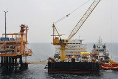 Supply boat transfer cargo to oil and gas industry and moving cargo from the boat to the platform. Boat waiting transfer cargo and passenger between oil and stock photos