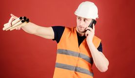 Supply of building materials concept. Engineer, architect, builder on busy face speak on phone, hold blueprints, copy. Space. Man, architect in helmet supervise royalty free stock images