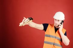 Supply of building materials concept. Engineer, architect on busy face speaks on phone, holds blueprints, pointing with. Finger, copy space. Man supervises royalty free stock photos