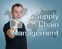 Supply Chain Management. Young man press digital Supply Chain Management button on interface in front of him Royalty Free Stock Images