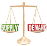 Supply and Demand Balance Scale Economics Principles Law. Supply and Demand words on a gold scale or balance to illustrate the principle law of a free market Royalty Free Stock Images