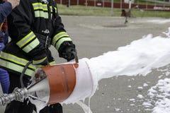 Supply of foam from a foam generator, fire extinguishing foam flies from the foam generator, which keeps the fireman in combat royalty free stock photo