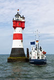 Supply ship at Roter Sand lighthouse. Supply ship moored at lighthouse Roter Sand in the german Wadden Sea Royalty Free Stock Image