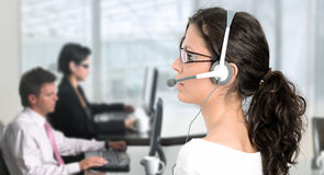 IT support. Pretty young woman works as an IT helpdesk operator Royalty Free Stock Photography