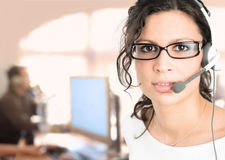 IT support. Young female customer service representative recieves calls on a headset while an IT specialist works on a computer in the background Royalty Free Stock Image