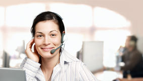 IT-support. Young and kind female customer cervice representative at an IT company Stock Photos