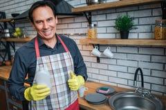 Support adulte gentil positif d'homme à l'évier dans la cuisine et pose sur la caméra Il tiennent le gel de lavage et le sourire  images stock