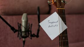 Support Artists Note Attached to Guitar Strings in Home Studio of Indie Musician