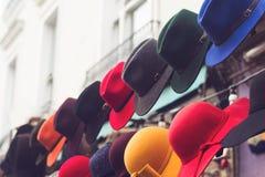 Support avec les chapeaux colorés sur l'entrée de magasin Photographie stock