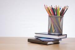 Support avec les crayons colorés se tenant sur des livres Photos libres de droits